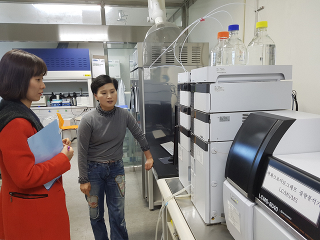 Photograph of two people looking at mass spectrometer.